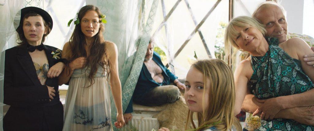 Meret Becker und Sabine Timoteo als Brautpaar, Karl Kranzkowski und Corinne Harfouch in Umarmung, im Vordergrund ein Kind