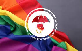 Logo Diskriminierungsschutz vor Regenbogenfahne mit Faltenwurf